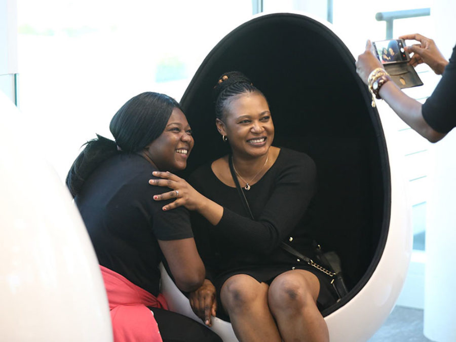 two woman in egg chairs getting picture taken